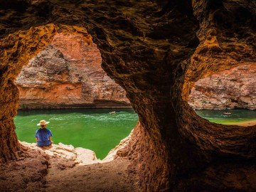 A lone man sits beneath an overhang near the Colorado River in Grand Canyon