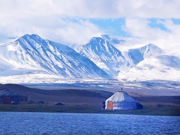 Tuvan gur (yurt) beneath the snow-covered mountains of Mongolia